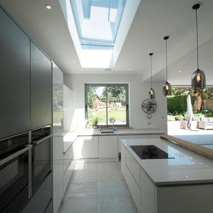 サリーの大きいコンテンポラリースタイルのおしゃれなキッチン (ドロップインシンク、フラットパネル扉のキャビネット、白いキャビネット、人工大理石カウンター、グレーのキッチンパネル、ガラス板のキッチンパネル、シルバーの調理設備の、クッションフロア、グレーの床、白いキッチンカウンター) の写真