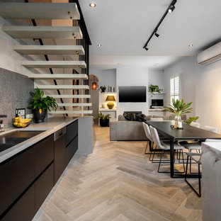 Mid-sized contemporary single-wall open plan kitchen in Melbourne with an undermount sink, black cabinets, marble benchtops, black splashback, mosaic tile splashback, stainless steel appliances, light hardwood floors and with island.