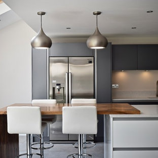 Photo of a mid-sized contemporary single-wall open plan kitchen in West Midlands with grey cabinets, quartzite benchtops, ceramic floors, with island, an undermount sink, flat-panel cabinets, stainless steel appliances, grey floor and grey benchtop.