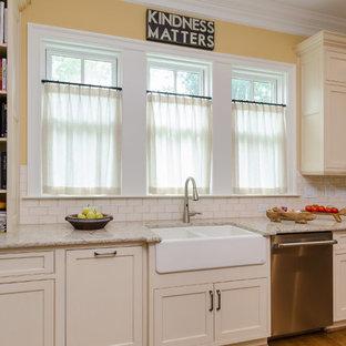 リッチモンドの中サイズのエクレクティックスタイルのおしゃれなキッチン (エプロンフロントシンク、落し込みパネル扉のキャビネット、白いキャビネット、御影石カウンター、ベージュキッチンパネル、セラミックタイルのキッチンパネル、シルバーの調理設備の、無垢フローリング、茶色い床) の写真