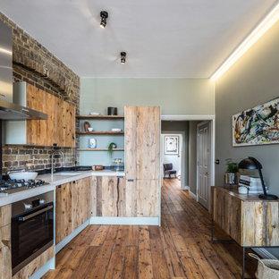Imagen de cocina en L, minimalista, pequeña, abierta, sin isla, con armarios con paneles lisos, puertas de armario de madera oscura, encimera de cemento, salpicadero marrón, salpicadero de ladrillos, electrodomésticos con paneles y suelo de madera en tonos medios