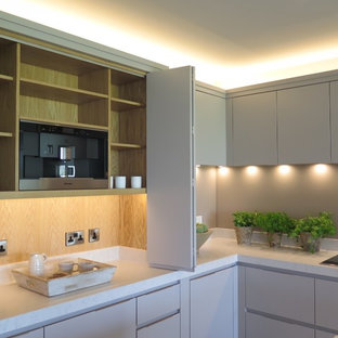 Inspiration for an expansive contemporary open plan kitchen in Cheshire with a double-bowl sink, flat-panel cabinets, grey cabinets, quartzite benchtops, grey splashback, glass sheet splashback, stainless steel appliances, porcelain floors and multiple islands.