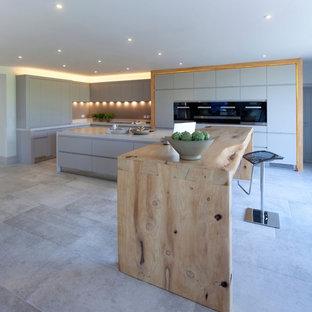 チェシャーの巨大なコンテンポラリースタイルのおしゃれなキッチン (ダブルシンク、フラットパネル扉のキャビネット、グレーのキャビネット、珪岩カウンター、グレーのキッチンパネル、ガラス板のキッチンパネル、シルバーの調理設備の、磁器タイルの床) の写真