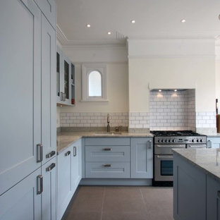 Design ideas for a large classic l-shaped kitchen/diner in London with a submerged sink, shaker cabinets, blue cabinets, granite worktops, ceramic splashback, stainless steel appliances, porcelain flooring, an island and white splashback.