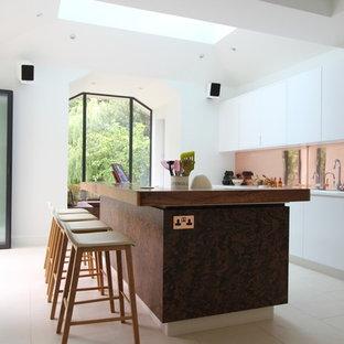 ロンドンの広いコンテンポラリースタイルのおしゃれなキッチン (アンダーカウンターシンク、フラットパネル扉のキャビネット、濃色木目調キャビネット、木材カウンター、シルバーの調理設備、セラミックタイルの床) の写真