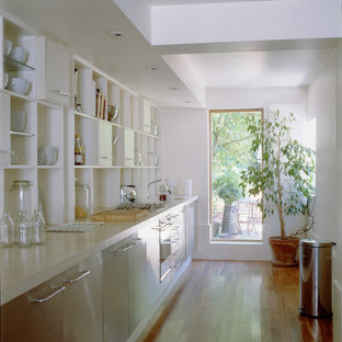 Photo of a small contemporary single-wall eat-in kitchen in Other with open cabinets, white cabinets, concrete benchtops, medium hardwood floors and no island.