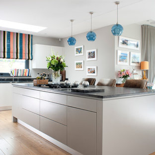 Contemporary kitchen in Essex with flat-panel cabinets, grey cabinets, medium hardwood flooring and an island.