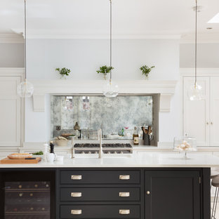 Photo of a mid-sized transitional l-shaped kitchen in London with quartzite benchtops, metallic splashback, mirror splashback, with island, an undermount sink, shaker cabinets, black cabinets and beige floor.