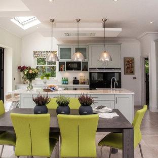 Große Moderne Wohnküche in L-Form mit Doppelwaschbecken, Schrankfronten im Shaker-Stil, blauen Schränken, Quarzit-Arbeitsplatte, schwarzen Elektrogeräten, Kalkstein, Kücheninsel und grauem Boden in Surrey