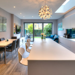 Photo of a medium sized contemporary single-wall open plan kitchen in London with flat-panel cabinets, white cabinets, an island, white worktops, a submerged sink and glass sheet splashback.