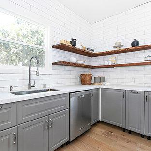 Transitional l-shaped light wood floor kitchen photo in Los Angeles with an undermount sink, raised-panel cabinets, gray cabinets, marble countertops, white backsplash, subway tile backsplash and stainless steel appliances