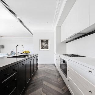 Diseño de cocina de galera, nórdica, con fregadero encastrado, armarios estilo shaker, puertas de armario blancas, electrodomésticos de acero inoxidable, suelo de madera en tonos medios, una isla y suelo marrón