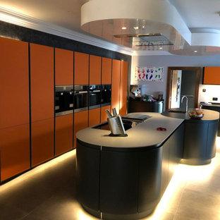他の地域の広いコンテンポラリースタイルのおしゃれなキッチン (ドロップインシンク、フラットパネル扉のキャビネット、オレンジのキャビネット、クオーツストーンカウンター、グレーのキッチンパネル、セラミックタイルのキッチンパネル、シルバーの調理設備、セラミックタイルの床、グレーの床、グレーのキッチンカウンター) の写真