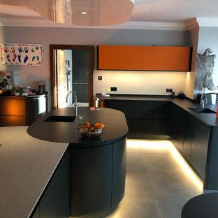 他の地域の大きいコンテンポラリースタイルのおしゃれなキッチン (ドロップインシンク、フラットパネル扉のキャビネット、オレンジのキャビネット、クオーツストーンカウンター、グレーのキッチンパネル、セラミックタイルのキッチンパネル、シルバーの調理設備の、セラミックタイルの床、グレーの床、グレーのキッチンカウンター) の写真