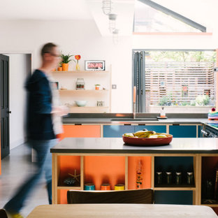 This is an example of a scandinavian u-shaped eat-in kitchen in Other with a single-bowl sink, flat-panel cabinets, orange cabinets, coloured appliances, concrete floors, a peninsula, grey floor and grey benchtop.