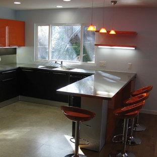 Ispirazione per una cucina minimal di medie dimensioni con lavello a doppia vasca, ante lisce, ante arancioni, top in acciaio inossidabile, paraspruzzi a effetto metallico, paraspruzzi con piastrelle di metallo, elettrodomestici in acciaio inossidabile, pavimento con piastrelle in ceramica e penisola
