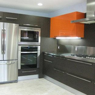 Foto di una cucina minimal con lavello integrato, ante lisce, ante arancioni, top in acciaio inossidabile, paraspruzzi marrone, paraspruzzi con piastrelle di metallo, elettrodomestici in acciaio inossidabile e pavimento in gres porcellanato