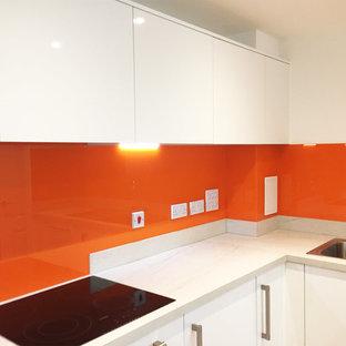 ハートフォードシャーの広いモダンスタイルのおしゃれなダイニングキッチン (フラットパネル扉のキャビネット、白いキャビネット、大理石カウンター、オレンジのキッチンパネル、ガラス板のキッチンパネル、アイランドなし) の写真