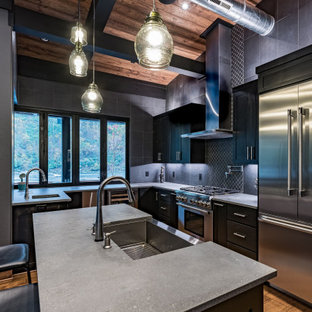 Mid-sized contemporary u-shaped eat-in kitchen in Phoenix with a farmhouse sink, recessed-panel cabinets, black cabinets, wood benchtops, grey splashback, slate splashback, stainless steel appliances, medium hardwood floors, with island, brown floor and brown benchtop.