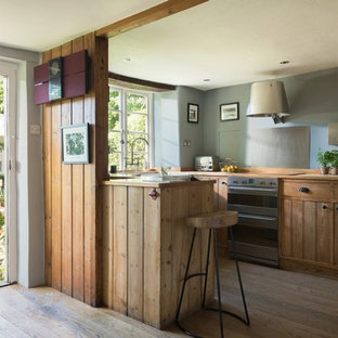 This is an example of a rural u-shaped kitchen in Other with louvered cabinets, medium wood cabinets, metallic splashback, medium hardwood flooring, a breakfast bar and brown floors.