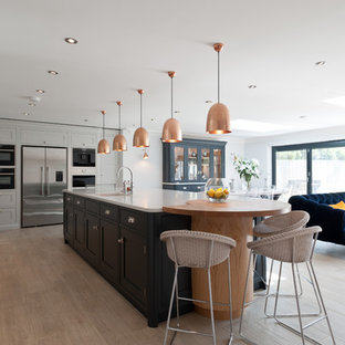This is an example of a large classic l-shaped open plan kitchen in Surrey with shaker cabinets, quartz worktops, an island, white worktops, a submerged sink, white cabinets, black appliances, light hardwood flooring and beige floors.