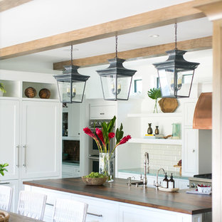 Large tropical eat-in kitchen remodeling - Example of a large island style u-shaped medium tone wood floor and brown floor eat-in kitchen design in Orange County with a double-bowl sink, shaker cabinets, white cabinets, wood countertops, white backsplash, subway tile backsplash, stainless steel appliances, an island and brown countertops