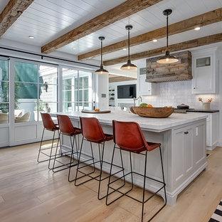 Coastal light wood floor kitchen photo in Orange County with white cabinets, white backsplash, an island and shaker cabinets