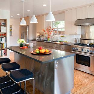 Idéer för ett avskilt, stort modernt linjärt kök, med en undermonterad diskho, släta luckor, skåp i rostfritt stål, rostfria vitvaror, ljust trägolv, en köksö, bänkskiva i kalksten, stänkskydd med metallisk yta, stänkskydd i metallkakel och brunt golv