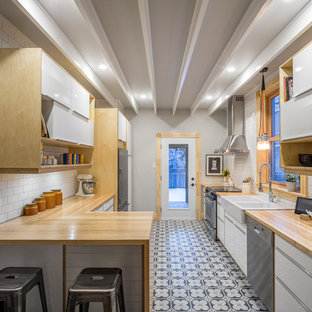 Diseño de cocina de galera, contemporánea, pequeña, cerrada, con fregadero sobremueble, armarios con paneles lisos, puertas de armario blancas, encimera de madera, salpicadero blanco, salpicadero de azulejos tipo metro, electrodomésticos de acero inoxidable, suelo de baldosas de cerámica y península