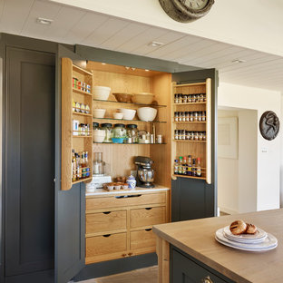 Design ideas for a large traditional kitchen pantry in Essex with grey cabinets, wood worktops and an island.