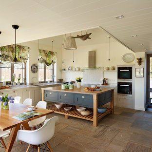Large coastal l-shaped open plan kitchen in Essex with grey cabinets, wood worktops and an island.