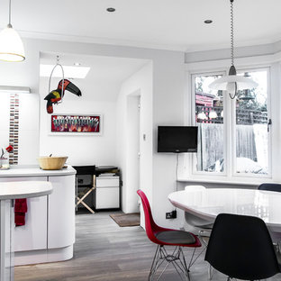 Contemporary kitchen ideas - Kitchen - contemporary galley laminate floor kitchen idea in London with flat-panel cabinets, white cabinets, solid surface countertops, red backsplash, glass sheet backsplash, paneled appliances and two islands