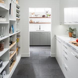 Diseño de cocina moderna, de tamaño medio, con despensa, armarios con paneles lisos, puertas de armario blancas, encimera de mármol, suelo de pizarra, suelo gris y encimeras blancas