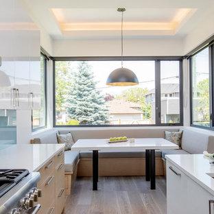 Foto på ett stort funkis vit kök, med en dubbel diskho, släta luckor, skåp i ljust trä, bänkskiva i kvarts, blått stänkskydd, glaspanel som stänkskydd, rostfria vitvaror, en köksö, ljust trägolv och beiget golv