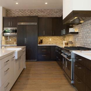 Imagen de cocina en L, minimalista, con fregadero sobremueble, armarios con paneles lisos, puertas de armario de madera en tonos medios, salpicadero de ladrillos, electrodomésticos con paneles, suelo de madera clara y una isla