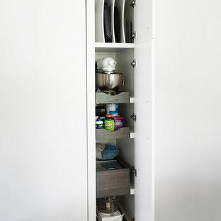 ニューヨークの中くらいのトランジショナルスタイルのおしゃれなキッチン (シングルシンク、フラットパネル扉のキャビネット、白いキャビネット、珪岩カウンター、茶色いキッチンパネル、レンガのキッチンパネル、シルバーの調理設備、磁器タイルの床、グレーの床) の写真