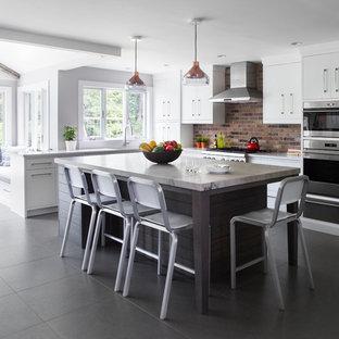ニューヨークの中サイズのトランジショナルスタイルのおしゃれなキッチン (シングルシンク、フラットパネル扉のキャビネット、白いキャビネット、珪岩カウンター、茶色いキッチンパネル、レンガのキッチンパネル、シルバーの調理設備の、磁器タイルの床、グレーの床) の写真