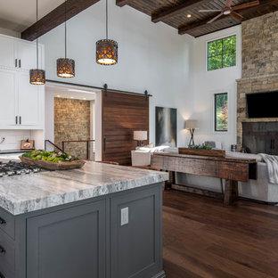 Foto på ett stort rustikt svart kök, med en undermonterad diskho, skåp i shakerstil, vita skåp, granitbänkskiva, vitt stänkskydd, fönster som stänkskydd, rostfria vitvaror, mörkt trägolv, en köksö och brunt golv