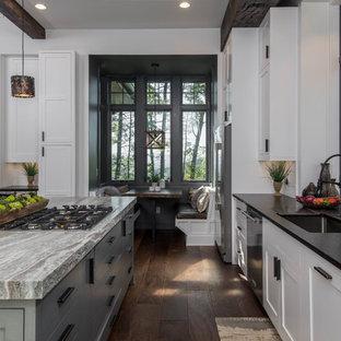 Foto di una grande cucina rustica con lavello sottopiano, ante in stile shaker, ante bianche, top in granito, paraspruzzi bianco, paraspruzzi a finestra, elettrodomestici in acciaio inossidabile, parquet scuro, pavimento marrone e top nero