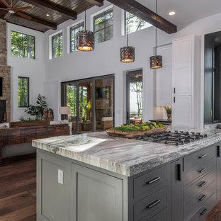 Große Urige Wohnküche in L-Form mit Schrankfronten im Shaker-Stil, weißen Schränken, Granit-Arbeitsplatte, Küchenrückwand in Weiß, Rückwand-Fenster, Küchengeräten aus Edelstahl, dunklem Holzboden, Kücheninsel, braunem Boden und schwarzer Arbeitsplatte in Sonstige