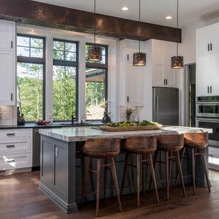 Inredning av ett rustikt stort svart svart kök, med en undermonterad diskho, skåp i shakerstil, vita skåp, granitbänkskiva, vitt stänkskydd, fönster som stänkskydd, rostfria vitvaror, mörkt trägolv, en köksö och brunt golv