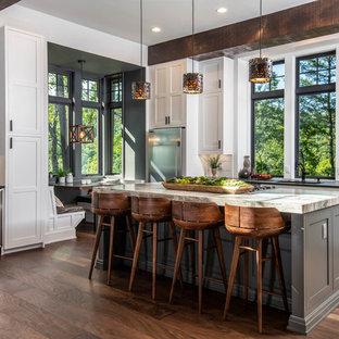 Große Rustikale Wohnküche in L-Form mit Schrankfronten im Shaker-Stil, weißen Schränken, Rückwand-Fenster, Küchengeräten aus Edelstahl, dunklem Holzboden, Kücheninsel, braunem Boden, schwarzer Arbeitsplatte, Unterbauwaschbecken, Granit-Arbeitsplatte und Küchenrückwand in Weiß in Sonstige