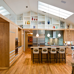 Modern open concept kitchen ideas - Inspiration for a modern open concept kitchen remodel in Minneapolis with stainless steel appliances, green backsplash, matchstick tile backsplash, flat-panel cabinets and light wood cabinets