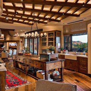 Aménagement d'une grande cuisine américaine parallèle sud-ouest américain avec un évier de ferme, un placard avec porte à panneau encastré, des portes de placard en bois brun, un plan de travail en calcaire, une crédence blanche, une crédence en mosaïque, un électroménager en acier inoxydable, un sol en bois brun, un îlot central et un sol marron.