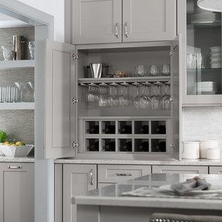 Cette photo montre une cuisine chic avec un placard à porte shaker, des portes de placard grises, un plan de travail en quartz modifié, une crédence blanche et un îlot central.