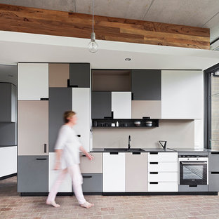 Contemporary kitchen inspiration - Trendy single-wall brick floor kitchen photo in Perth with a double-bowl sink, flat-panel cabinets, gray backsplash, stainless steel appliances and no island