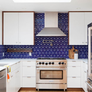 Design ideas for a midcentury kitchen in San Francisco with an undermount sink, flat-panel cabinets, white cabinets, quartz benchtops, blue splashback, ceramic splashback, stainless steel appliances, a peninsula, white benchtop and light hardwood floors.