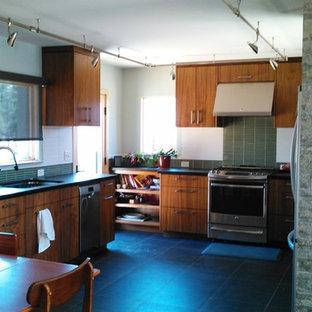 Idee per una cucina moderna con lavello sottopiano, ante lisce, ante in legno scuro, paraspruzzi verde, paraspruzzi con piastrelle di vetro, elettrodomestici in acciaio inossidabile, pavimento in gres porcellanato, nessuna isola, pavimento nero e top nero