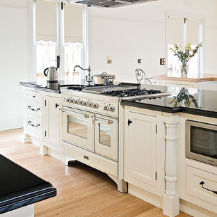 This is an example of a large traditional galley open plan kitchen in Sydney with a farmhouse sink, recessed-panel cabinets, white cabinets, white appliances, light hardwood floors and multiple islands.