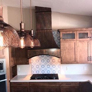 フェニックスの中サイズのラスティックスタイルのおしゃれなキッチン (アンダーカウンターシンク、シェーカースタイル扉のキャビネット、中間色木目調キャビネット、クオーツストーンカウンター、白いキッチンパネル、セメントタイルのキッチンパネル、シルバーの調理設備、コルクフローリング、ベージュの床、マルチカラーのキッチンカウンター) の写真
